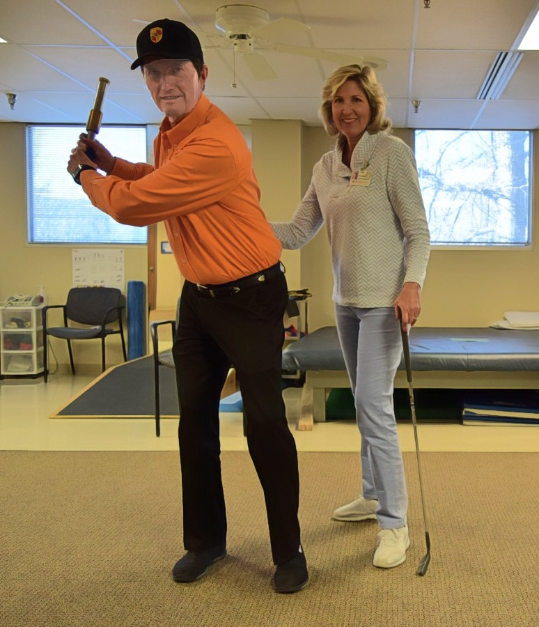 Overton in golf-swinging pose stands in front of therapist Suzanne Moskal.