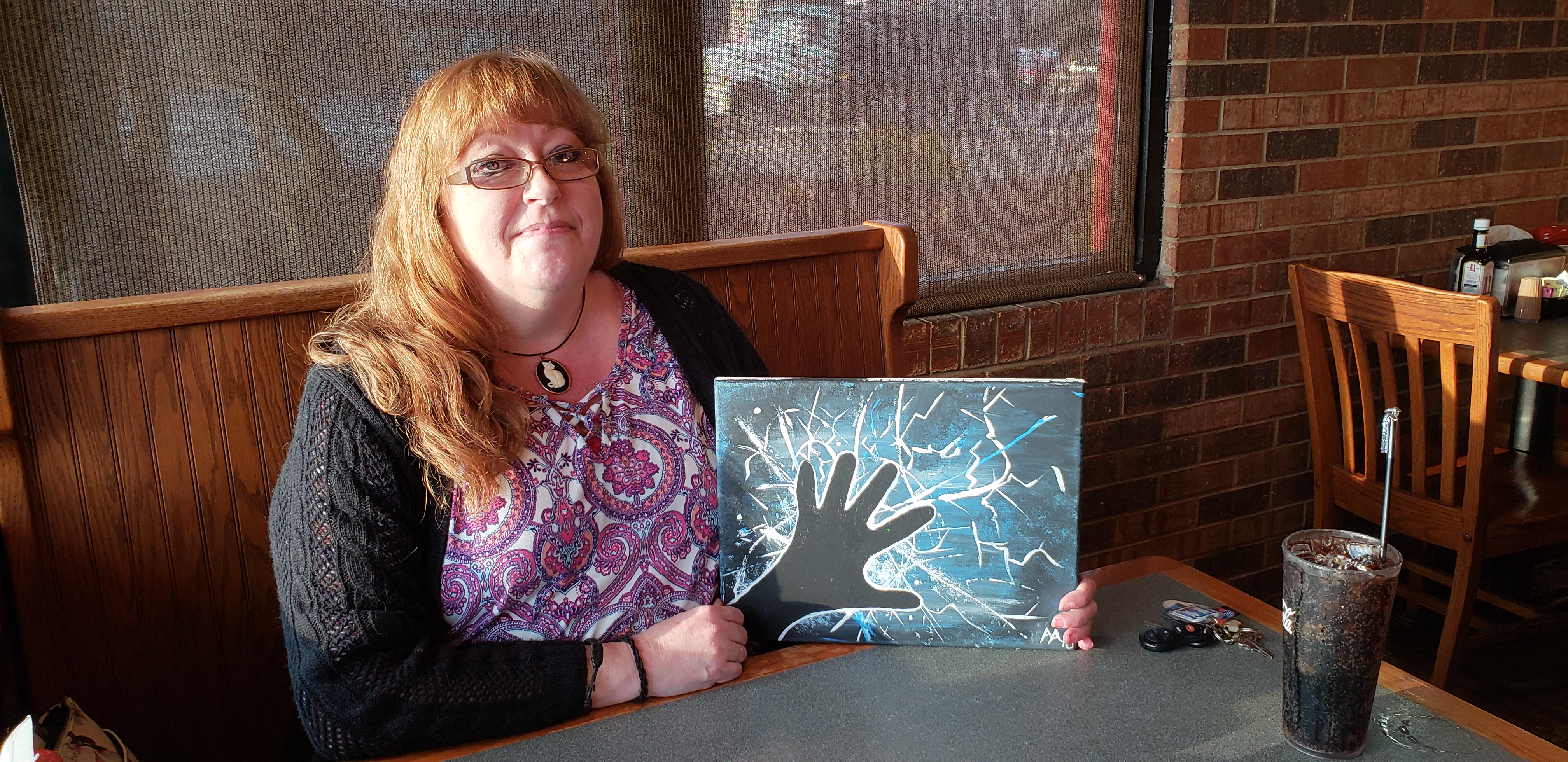 Peninsula patient Andee Anderson shows her first painting of a hand reaching out of the darkness.
