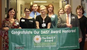 DAISY Committee with winner April Collins. Holding green DAISY banner in front.