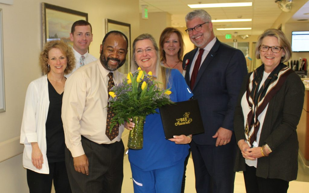 Administrative team, doctor and Micki Smith with tulips and BEE certificate.