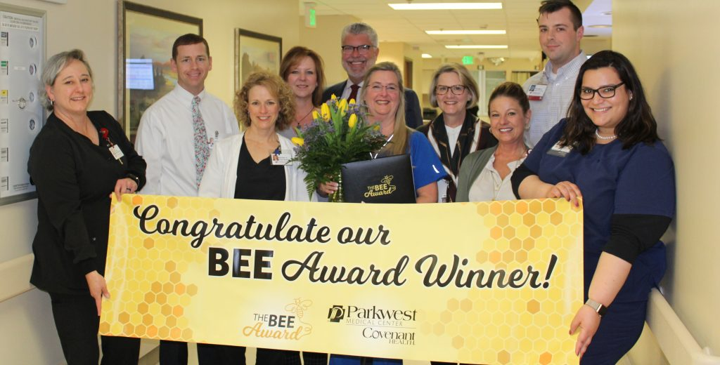 BEE Committee holding banner with winner.