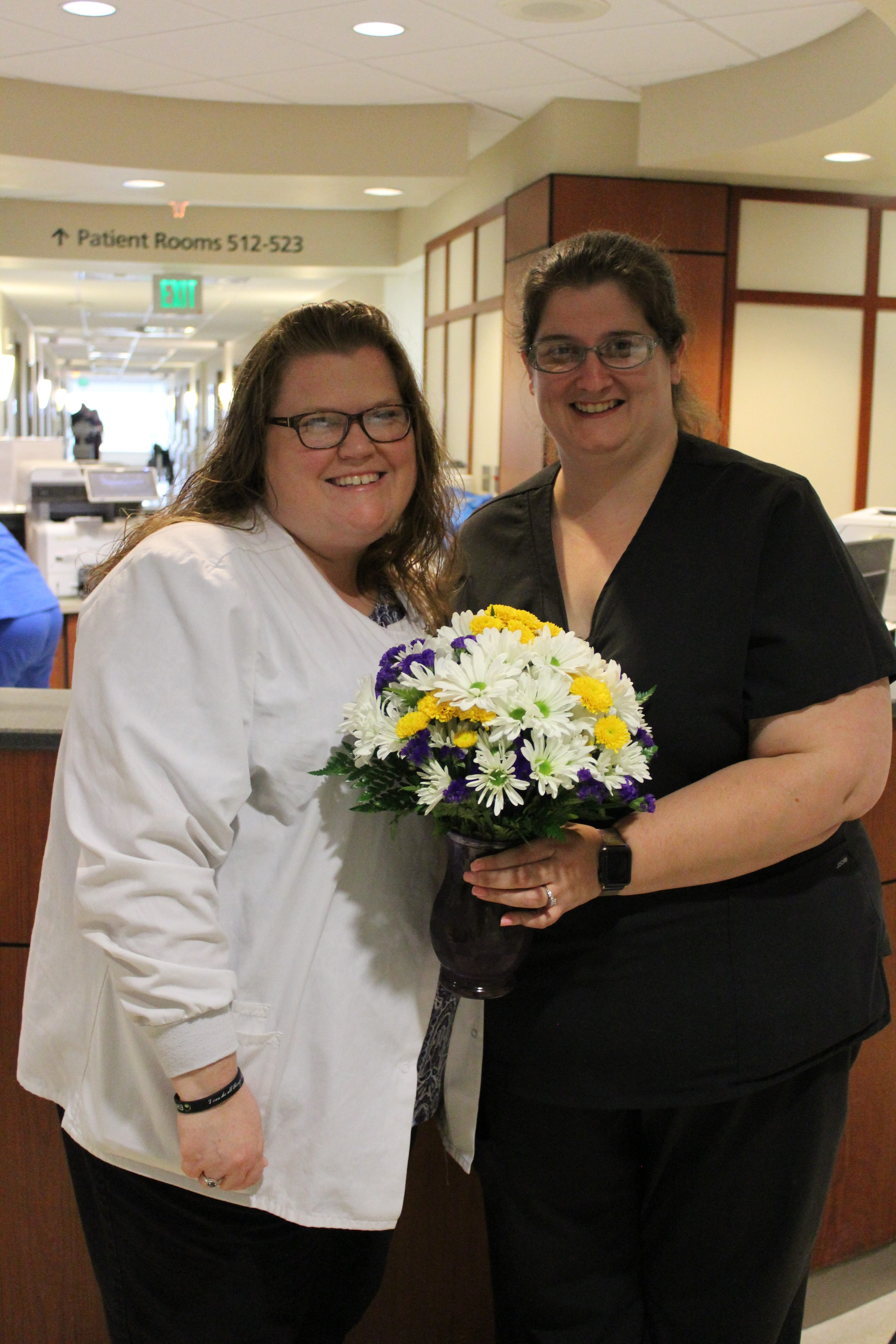 5R Nurse manager Crystal with Heather SCudder, holding daisies.