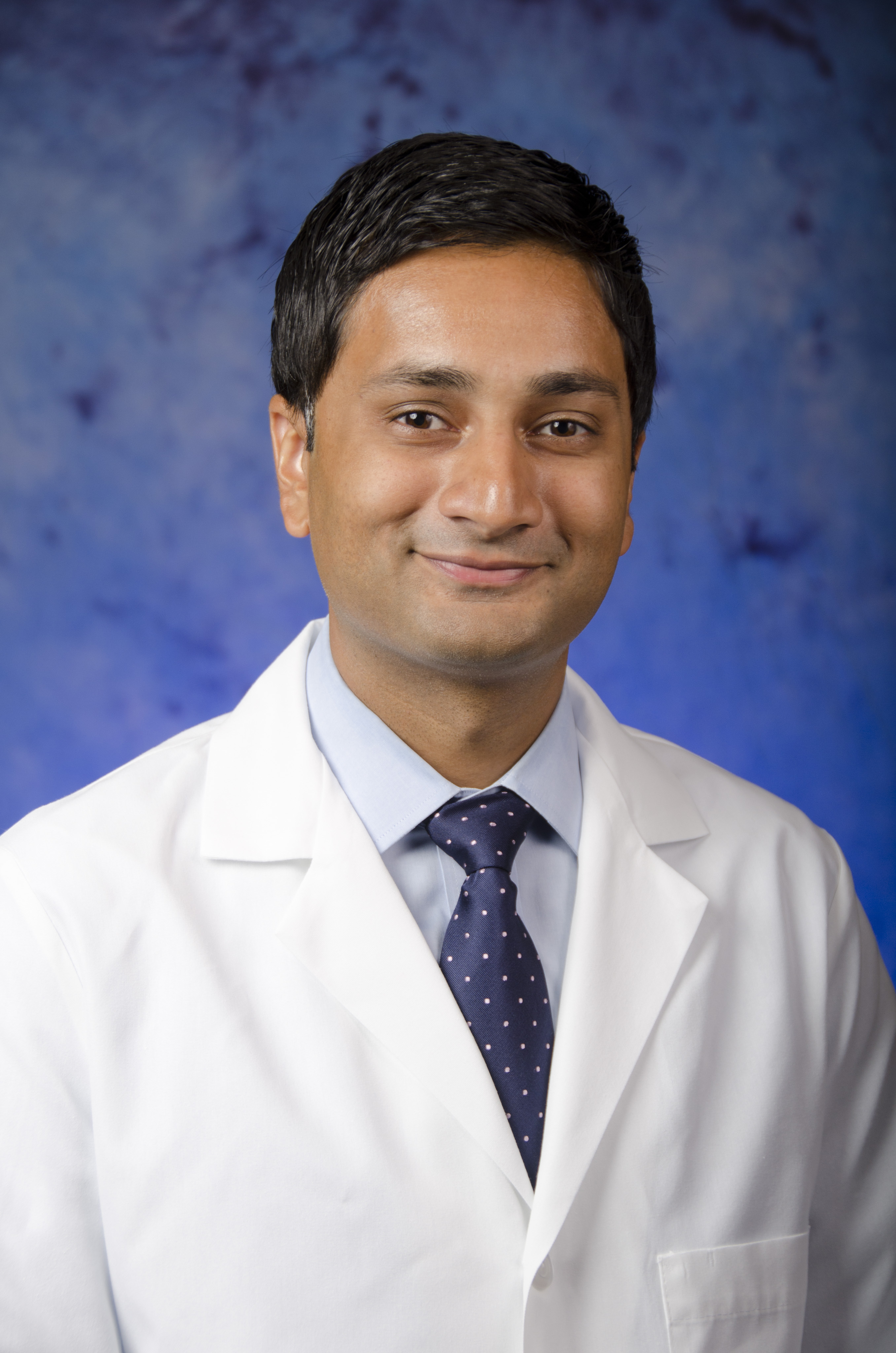 Dr. Ayaz Rahman in white lab coat, and tie.