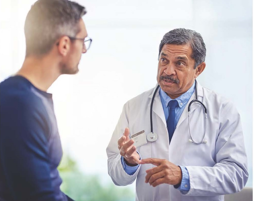 doctor in white lab coat talking with male patient in blue sweater.