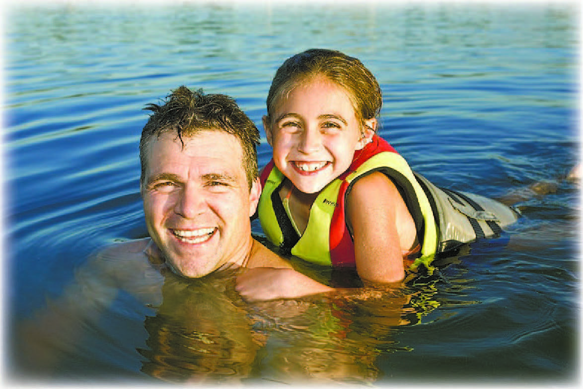 Dad and daughter swimming in water with lifejackets on.