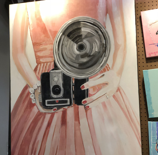 PAstel of lady in pink dress taking a photograph.