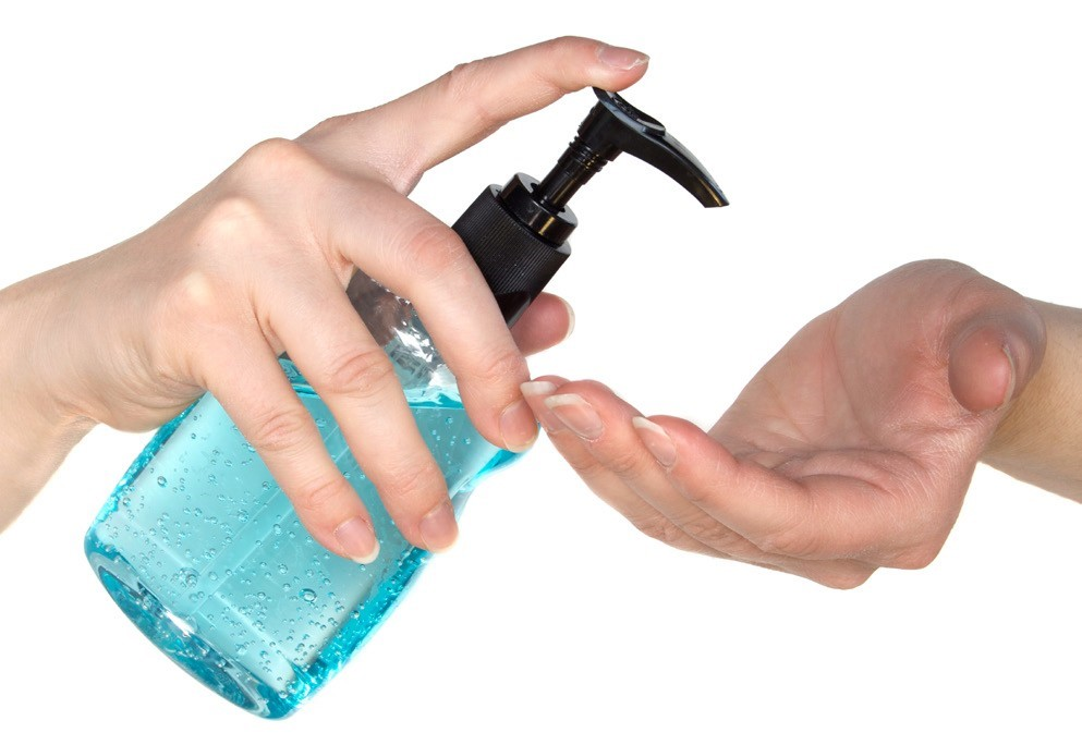 Bottle of hand sanitizer pumping into hand.