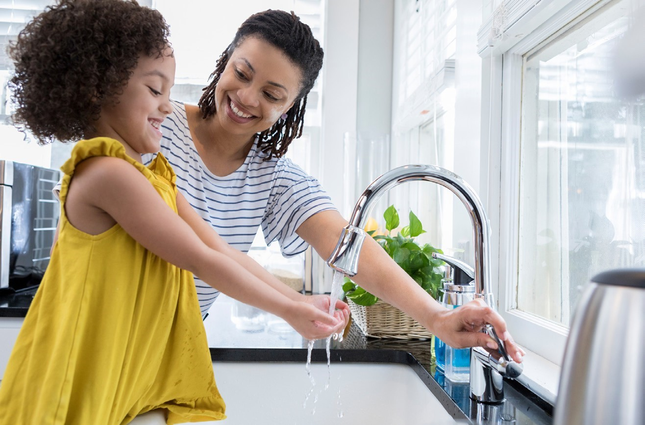 mom and daughter washing hands together at ktichen sink.
