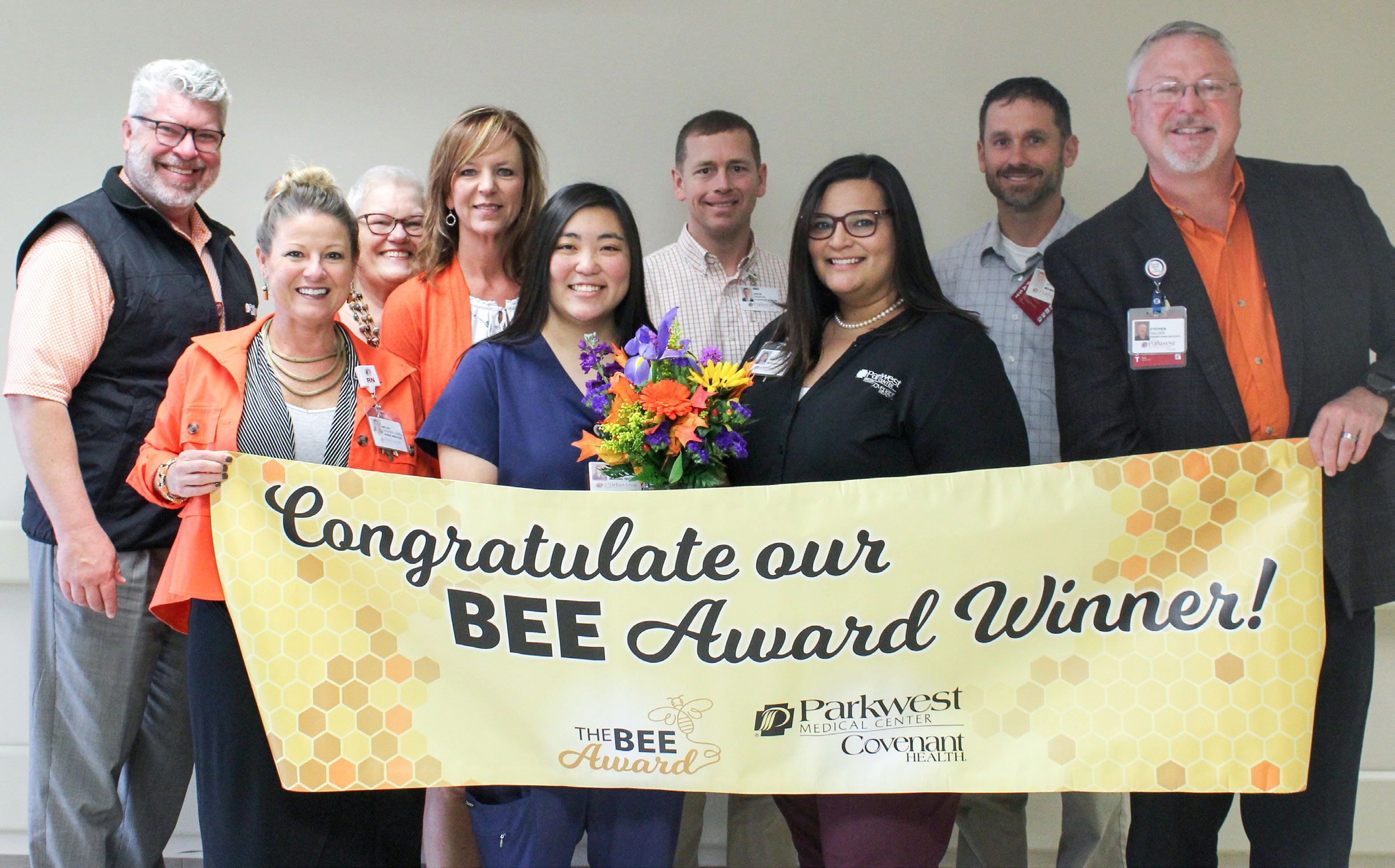 Laci Crass with department leadership and BEE Committee with BEE banner.