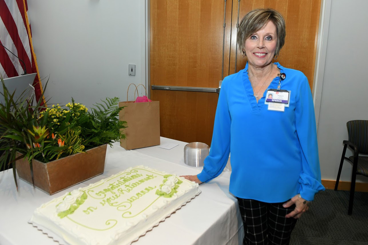 Suzanne Blocker with cake at retirement party