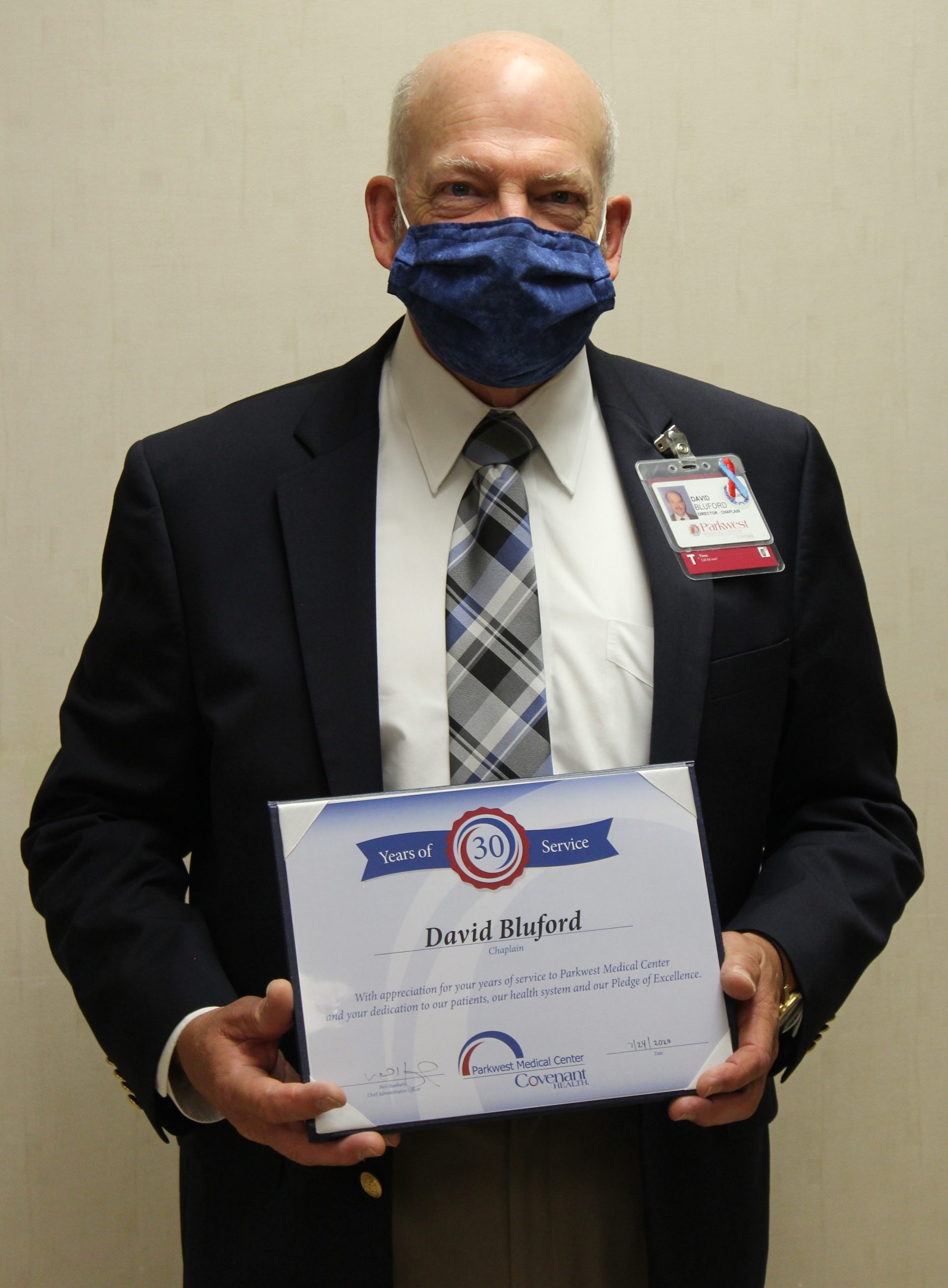 David Bluford in mask, holding certificate.