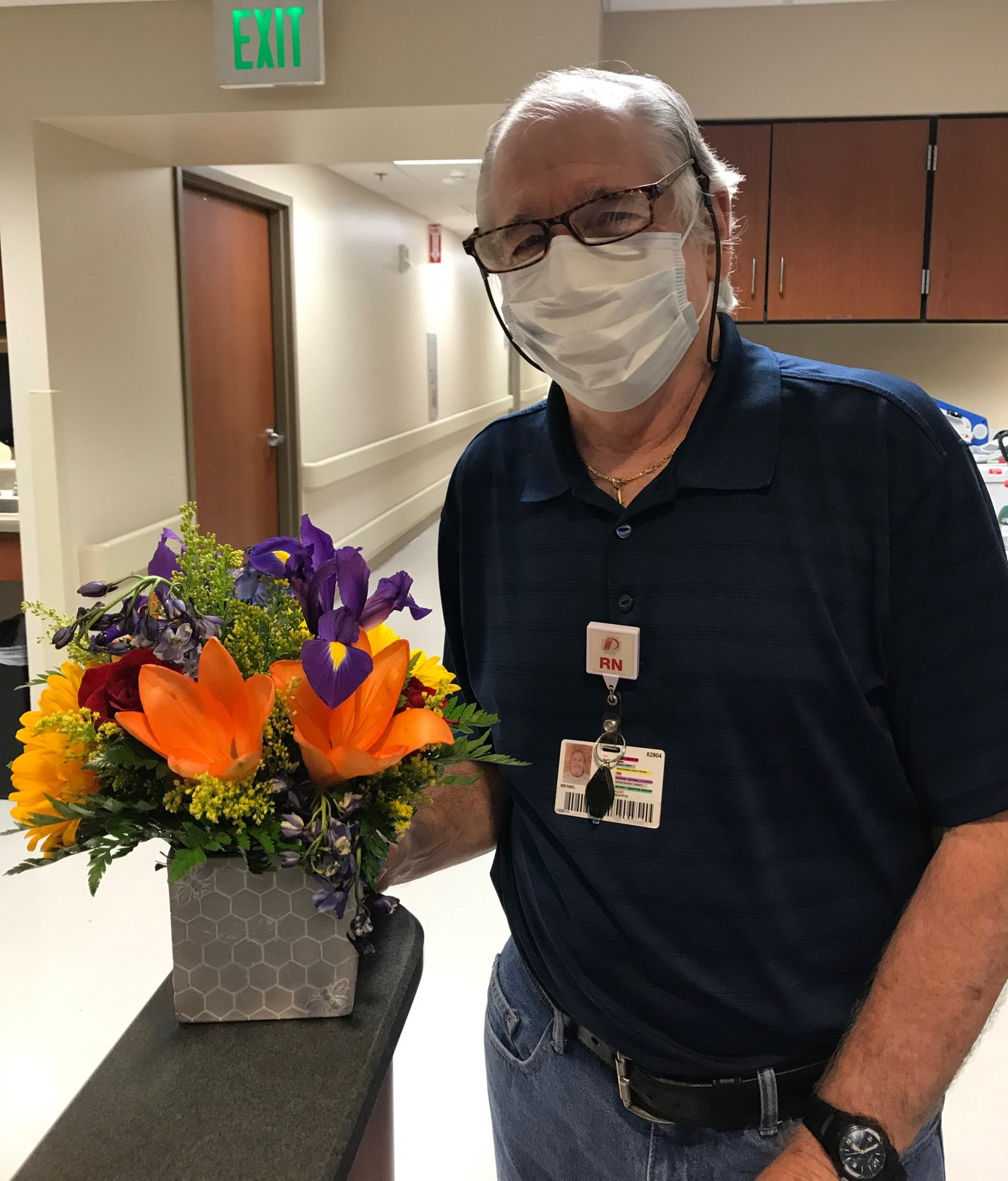 Mike Lauderdale with flowers and mask.
