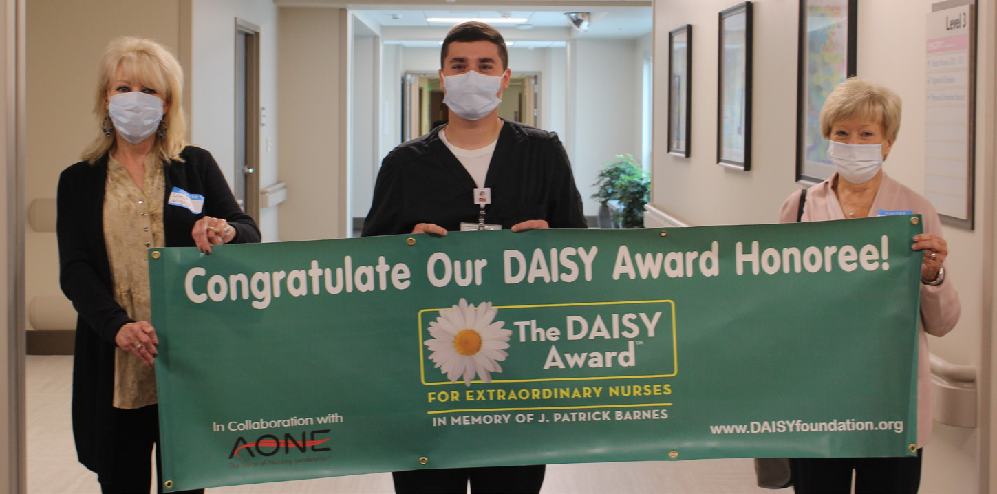 Matt Ryan pictured with DAISY banner held by the sisters who nominated him.