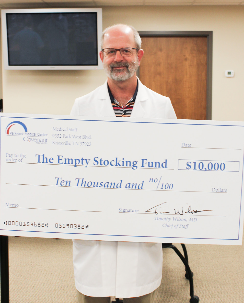 Dr. Wilson in lab coat holding big check for the Empty Stocking Fund.