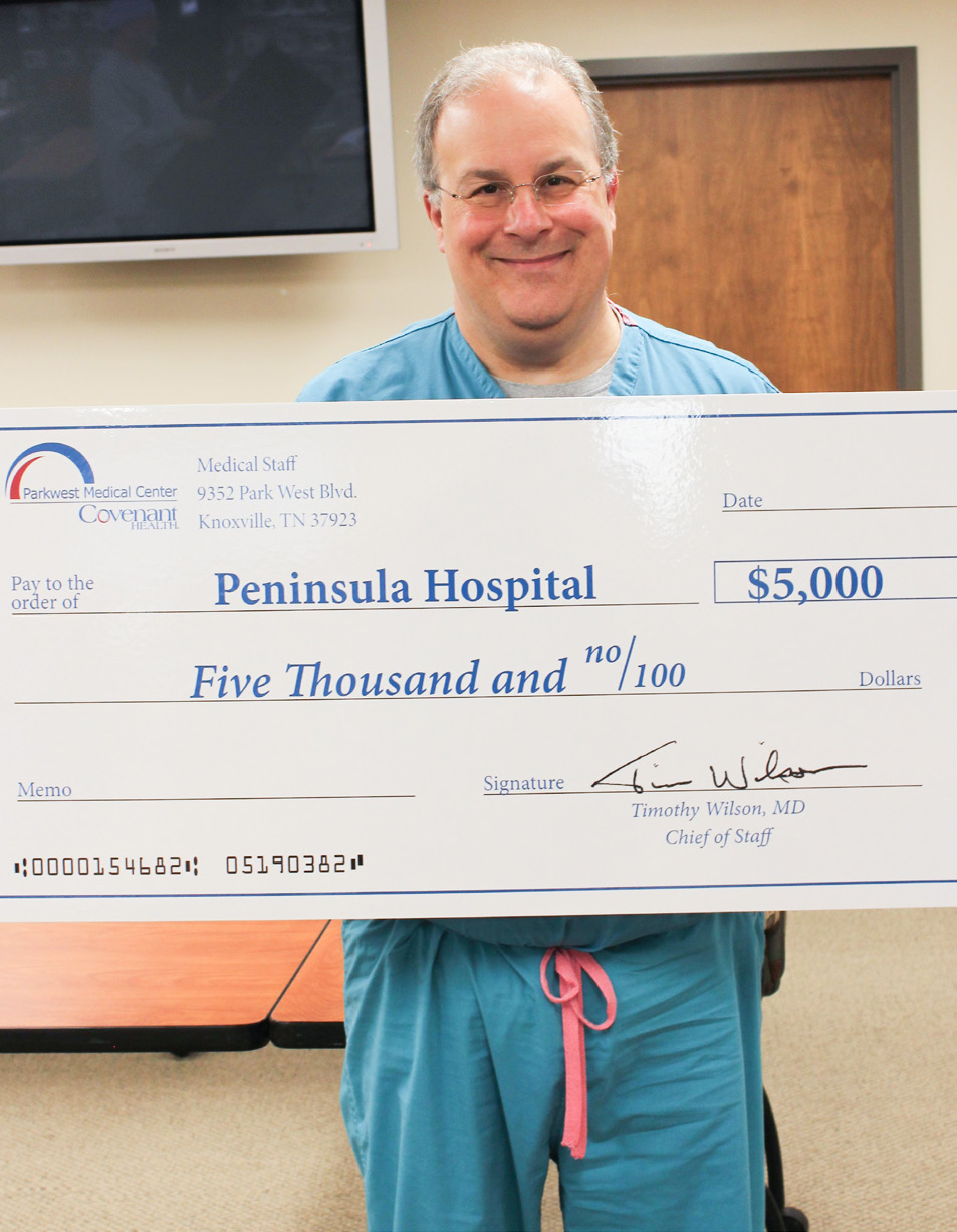 Dr. Roesch in scrubs holding big check for Peninsula Hospital.