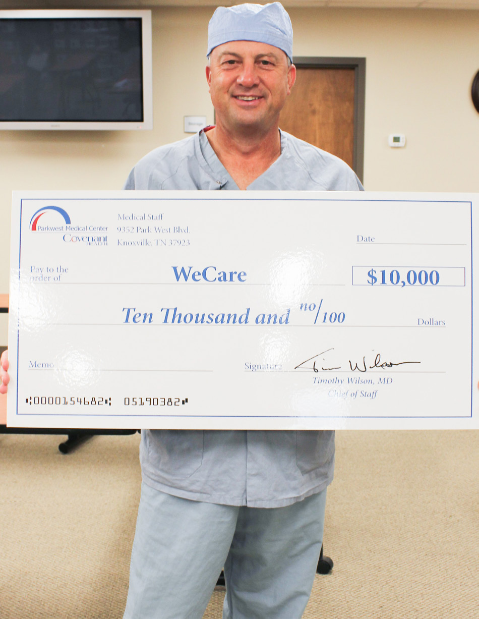Dr. Fuqua in scrubs holding big check for WeCare