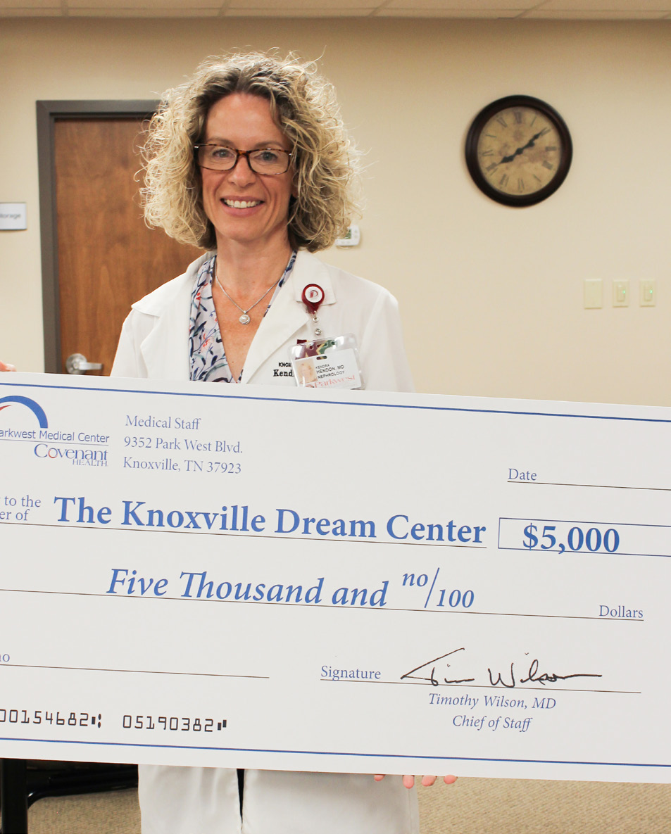 Dr. Kendra Hendon in labcoat holding big check for Knoxville Dream Center.