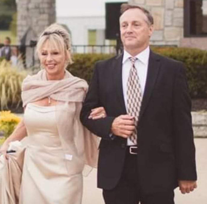 Charlene and her husband in dress clothes.