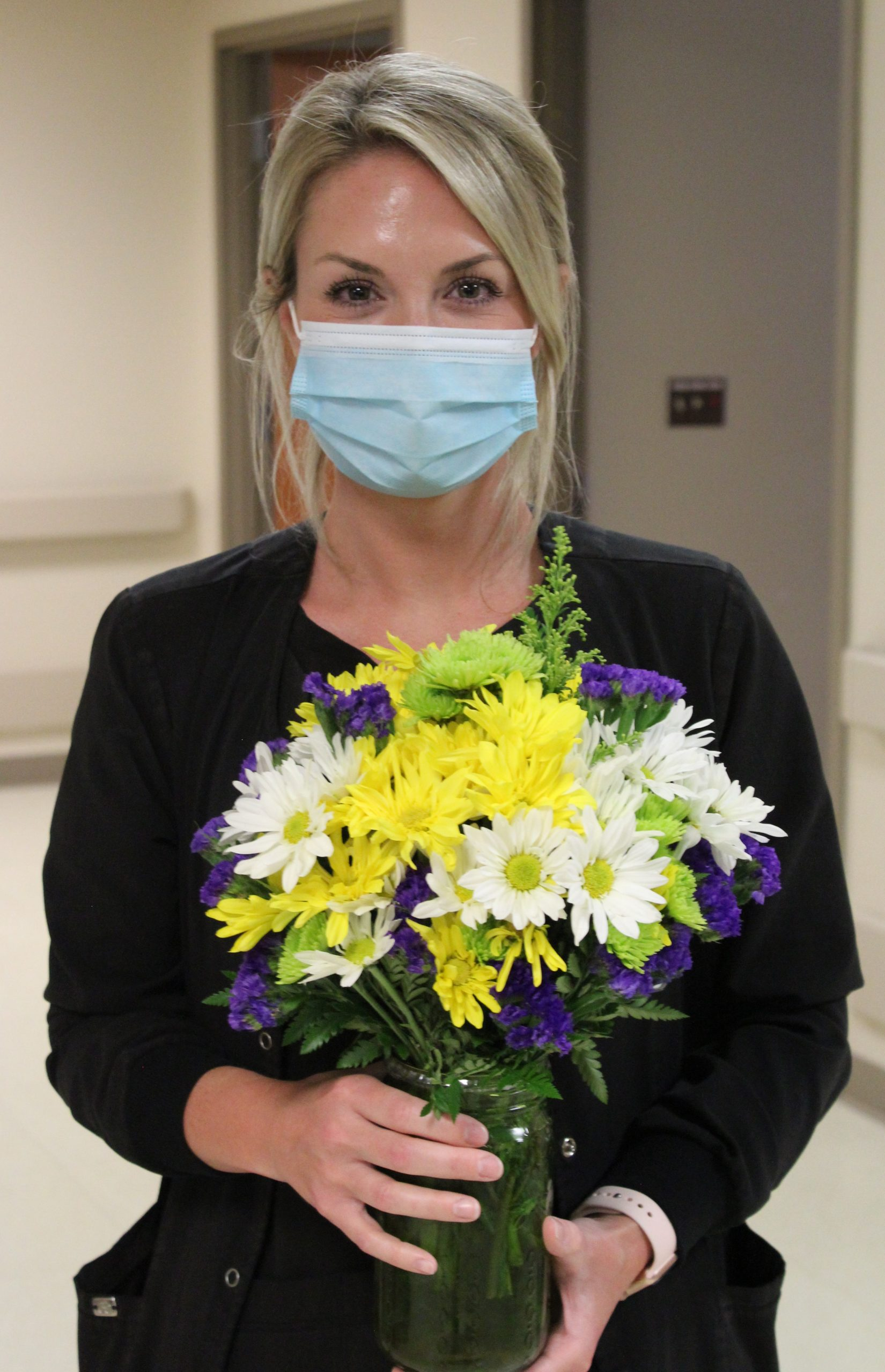 Nurse Laura Ivey dressed in black scrubs holding yellow and white daisies.
